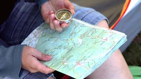 Female hands with map and compass. Woman sits in tent and holds travel map and compass with moving needle, pointing and searching route, direction and stock video