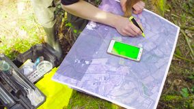 Female hands marking waypoints on the map. Close up female hands finding and marking waypoints on the map with smart phone stock footage