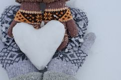 Female hands in mittens and baby hands in mittens keep the heart out of the snow against the background of white snow Royalty Free Stock Photography