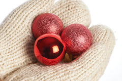 Female hands in mittens with Christmas balls isolated Royalty Free Stock Image