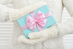 Female hands in mittens holding gift box Stock Photo