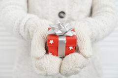 Female hands in mittens holding red gift box Royalty Free Stock Photos