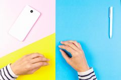 Female hands, mobile smart phone and white pen on yellow, blue and pink background. royalty free stock photo