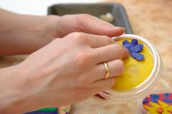 Female hands mold from a plasticine flower Stock Photography
