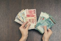 Female hands with money of south-east Asia. Currency of Hong Kong, Indonesia, Malaysia, Thai, Singapore. Travel, banking concept Royalty Free Stock Photo