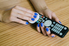 Female hands with a napkin wipe the remote control at the wooden Royalty Free Stock Photos