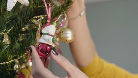 Female hands neatly hanging festive snowman toy on beautiful Christmas tree. Stock footage stock video footage