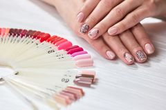 Female hands with nude manicure. Young woman hands with fresh beige manicure next to polish palette. Womens beauty and care Stock Photos