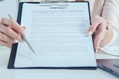 Female hands offer contract form on clipboard pad and silver pen to sign closeup. Strike a bargain for profit white collar motivation union decision corporate royalty free stock photography