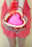 Female hands offering pink heart in small knitted basket Royalty Free Stock Photos