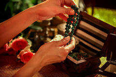 Female hands open box and touch bead decorations. Royalty Free Stock Photos