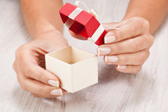 Female hands open a little gift Royalty Free Stock Photo