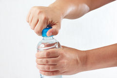 Female hands opening a bottle of fresh water Royalty Free Stock Images