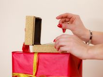 Female hands opening golden gift box with jewel pearls. Woman hands red nails manicure opening golden gift box with jewel pearls. Christmas time, giving and Stock Photography