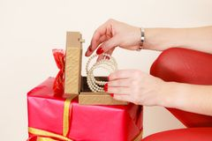 Female hands opening golden gift box with jewel pearls. Woman hands red nails manicure opening golden gift box with jewel pearls. Christmas time, giving and Royalty Free Stock Image