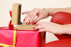Female hands opening golden gift box with jewel pearls. Woman hands red nails manicure opening golden gift box with jewel pearls. Christmas time, giving and Royalty Free Stock Photo
