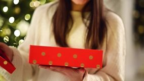 Female Hands Opening Red Box at Home. Unrecognizable Brunette Opening Christmas Gift. Blurred Xmas Lights on Background. stock video