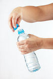 Female hands opening a small bottle of fresh water Royalty Free Stock Photo