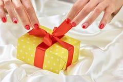 Female hands opening yellow box. Stock Photos