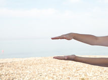 Female hands over the sea background Stock Photography