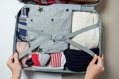 Female hands packed clothes in suitcase. Winter vacations and ho Stock Photos