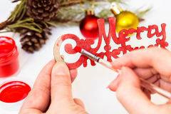 Female hands paint in red on the inscription Merry Christmas.Christmas decoration. Royalty Free Stock Photo