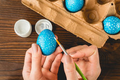 Female hands painted blue Easter eggs with a brush, top view Royalty Free Stock Photos