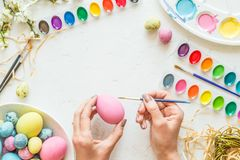 Female hands painting easter eggs. Holiday concept. Flat lay. Top view. stock images