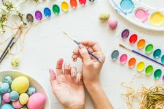 Female hands painting easter eggs. Holiday concept. Flat lay. Top view. royalty free stock photo