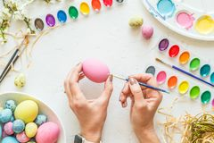 Female hands painting easter eggs. Holiday concept. Flat lay. Top view. stock photos