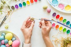 Female hands painting easter eggs. Holiday concept. Flat lay. Top view royalty free stock photo