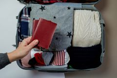 Female hands with passports on the background Open suitcase pack. Ed for travelling. Winter vacations and holidays. Top view Royalty Free Stock Images