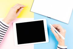 Female hands with pen, open notebook and tablet computer over yellow, blue and pink background.  Royalty Free Stock Photography