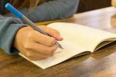 Female hands with pen writing on notebook Royalty Free Stock Photo