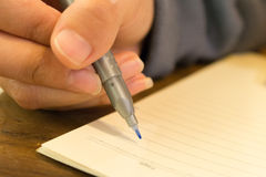 Female hands with pen writing on notebook Stock Image