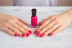 Female hands with pink manicure and a bottle of lacquer on a woo Stock Images