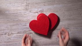 Female hands placing two red hearts on a wooden table, top view. Date, love, Valentine's day, concepts. 4K video. Young woman placing two red hearts on a wooden stock video