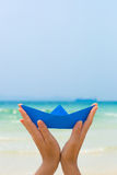 Female hands playing with blue paper boat on the beach. Female hands playing with blue paper boat on the white sand beach on blue sea background stock images