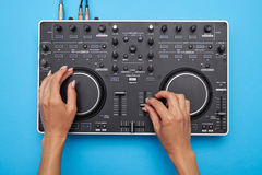 Female hands playing DJ mixer on blue background stock image
