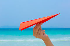 Female hands playing with paper plane on the beach. Female hands playing with paper plane in water on the white sand beach on blue sea background royalty free stock photo