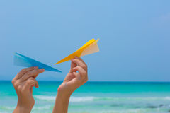 Female hands playing with paper planes on the beach. On blue sea background royalty free stock photos