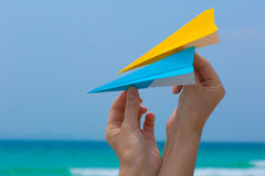 Female hands playing with paper planes on the beach. On blue sea background Stock Photos