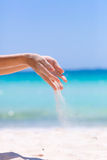 Female hands playing in the sand. On blue sea and sky background royalty free stock photos