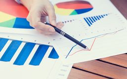 Female hands pointing with pen at business financial report graphic stock photos