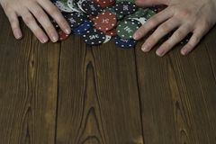 Female hands and poker chips on a wooden background stack royalty free stock photography