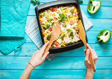Female hands poured baked pasta with broccoli and cheesy tomato sauce Royalty Free Stock Photos