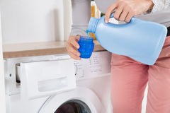 Female Hands Pouring Detergent In The Bottle Cap. Close-up Of Female Hands Pouring Detergent In The Blue Bottle Cap Stock Photo
