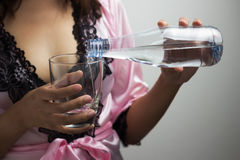 Female hands pouring water into a glass Royalty Free Stock Image