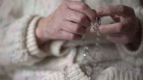 Female hands praying with crystal rosary stock footage