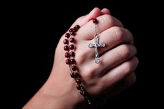 Female hands praying holding a rosary with Jesus Christ in the cross or Crucifix on black background. Woman with Christian Catholic religious faith Royalty Free Stock Photos